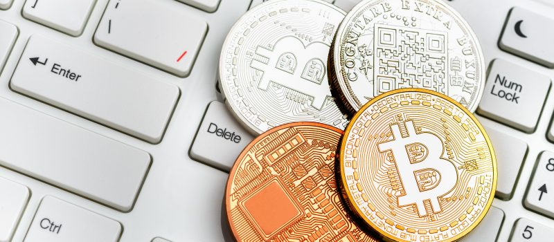 Moscow, Russia - July 19, 2017: Bitcoin Simbol Over Dollar And Euro Background